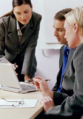 Two business women helping a business man at a laptop.